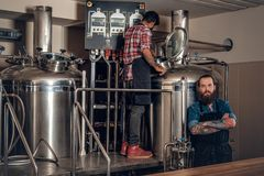 Hombres caucásicos e indios tatuados, barbudos en el microbrewery de la cerveza del arte Foto de archivo