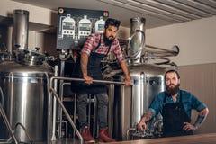 Hombres caucásicos e indios tatuados, barbudos en el microbrewery de la cerveza del arte Fotos de archivo