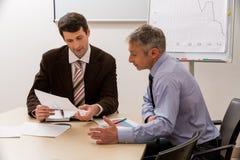 Hombres con interés de discutir el plan empresarial Foto de archivo libre de regalías