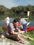 Hombres con la canoa en la naturaleza l Fotografía de archivo