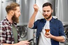 Hombres con la cerveza del arte de la prueba de la pipeta en la cervecería fotos de archivo