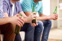 Hombres con las botellas de cerveza que se sientan en el sofá en casa Imagen de archivo libre de regalías
