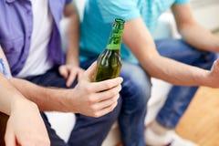 Hombres con las botellas de cerveza que se sientan en el sofá en casa Fotografía de archivo libre de regalías