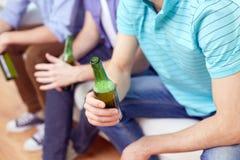 Hombres con las botellas de cerveza que se sientan en el sofá en casa Fotografía de archivo