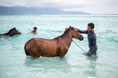 Hombres con los caballos en el mar Fotografía de archivo libre de regalías