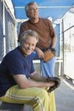 Hombres con los mitones en cobertizo del béisbol Imagenes de archivo