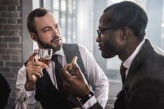 Hombres confiados con el cigarro y el vidrio de hablar de la bebida del alcohol foto de archivo