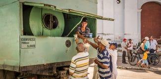 Hombres cubanos que compran cerveza de un camión Imagen de archivo