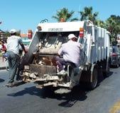 Hombres de basura detrás del camión de basura Fotos de archivo libres de regalías