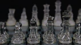 Hombres de cristal del ajedrez en la posición de salida a bordo con el fondo negro metrajes