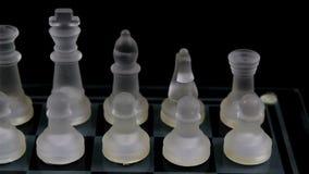 Hombres de cristal del ajedrez en la posición de salida a bordo con el fondo negro almacen de metraje de vídeo