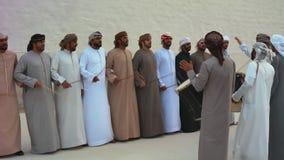 Hombres de Emirati que realizan el Yowla, una danza tradicional en la herencia de los United Arab Emirates al lado de un edificio metrajes