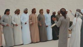 Hombres de Emirati que realizan el Yowla, una danza tradicional en la herencia de los United Arab Emirates al lado de un edificio almacen de metraje de vídeo