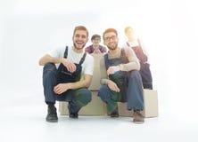 Hombres de entrega jovenes sonrientes que sostienen la pila de cajas Aislado en blanco Fotos de archivo libres de regalías