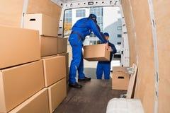 Hombres de entrega que cargan las cajas de cartón Fotos de archivo