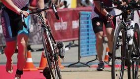 Hombres de funcionamiento con las bicicletas en triathlon metrajes