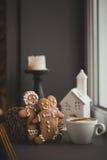 Hombres de la galleta del pan de jengibre en una taza caliente de capuchino Imagen de archivo libre de regalías
