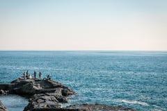 Hombres de la pesca en rocas por el océano japonés Foto de archivo libre de regalías