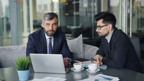 Hombres de los colegas en trajes que hablan en café durante almuerzo de negocios usando el ordenador portátil metrajes