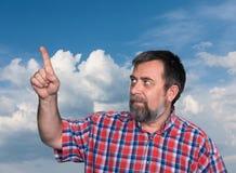 Hombres de mediana edad que señalan su índice hacia un cielo azul fotos de archivo