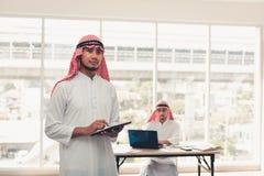 Hombres de negocios árabes que trabajan en línea con los wi de la tableta y de la tecnología fotos de archivo libres de regalías