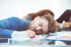 Hombres de negocios aburridos que duermen en un colega de la reunión Imagenes de archivo