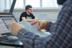 Hombres de negocios acertados en el trabajo en oficina Varones amistosos de la Edad Media que trabajan en oficina Estudiantes que foto de archivo