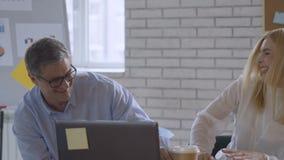Hombres de negocios acertados felices en la oficina que tiene documentos que lanzan de la diversi?n, c?mara lenta almacen de metraje de vídeo