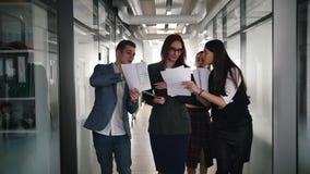 Hombres de negocios acertados que caminan a través del pasillo Gente que muestra los documentos a su jefe de la mujer metrajes