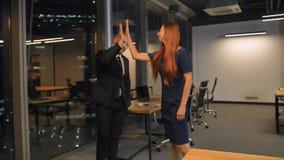 Hombres de negocios acertados que dan arriba cinco en la oficina, cámara lenta metrajes