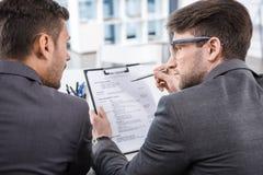 Hombres de negocios acertados que discuten el competidor de la entrevista de trabajo imagen de archivo libre de regalías
