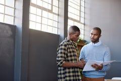 Hombres de negocios africanos enfocados que discuten el papeleo junto en una oficina Imagen de archivo