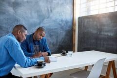 Hombres de negocios africanos jovenes en el trabajo en una oficina Imágenes de archivo libres de regalías