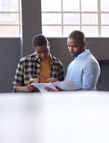 Hombres de negocios africanos que hablan sobre papeleo junto en una oficina Fotografía de archivo libre de regalías