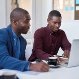 Hombres de negocios africanos que trabajan en un ordenador portátil en una oficina blanca Foto de archivo libre de regalías