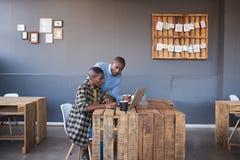 Hombres de negocios africanos que trabajan en un ordenador portátil junto en una oficina Fotos de archivo