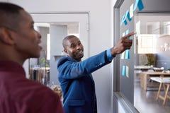 Hombres de negocios africanos strategizing con las notas pegajosas sobre una pared de cristal Foto de archivo libre de regalías