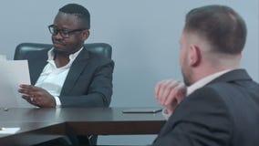Hombres de negocios afroamericanos serios que trabajan a través de los papeles y que discuten informe financiero con su socio almacen de video