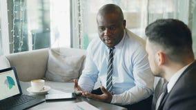 Hombres de negocios afroamericanos y caucásicos que miran cartas y diagramas en el ordenador portátil y la discusión financiera almacen de video