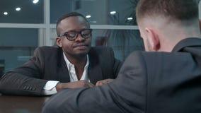 Hombres de negocios afroamericanos y cauc?sicos pensativos que trabajan a trav?s de los papeles y que discuten el informe financi almacen de metraje de vídeo