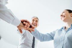 Hombres de negocios alegres que apilan las manos Foto de archivo libre de regalías