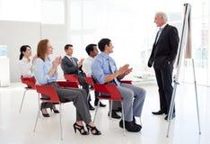 Hombres de negocios alegres que aplauden en una conferencia Imágenes de archivo libres de regalías