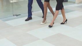 Hombres de negocios alegres que caminan junto a lo largo del pasillo de la oficina Cámara lenta almacen de metraje de vídeo