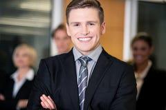 Hombres de negocios amistosos con el líder de sexo masculino en frente Imagen de archivo