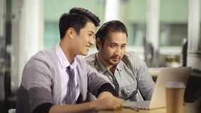 Hombres de negocios asiáticos que celebran éxito y el logro