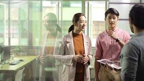 Hombres de negocios asiáticos que charlan en oficina almacen de video