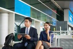 Hombres de negocios asiáticos que esperan en aeropuerto Imágenes de archivo libres de regalías