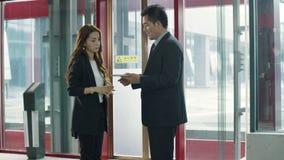 Hombres de negocios asiáticos que hablan en pasillo del elevador almacen de video