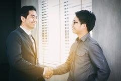 Hombres de negocios asiáticos que sacuden las manos y que sonríen su acuerdo imagen de archivo
