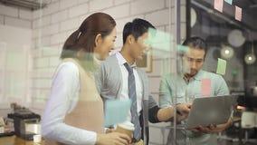 Hombres de negocios asiáticos que se encuentran en oficina almacen de metraje de vídeo